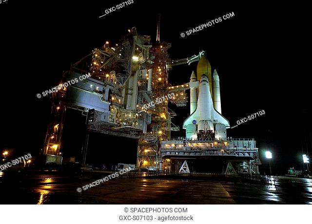 12/03/2001 -- Rain on the ground around Space Shuttle Endeavour on Launch Pad 39B reflects the many lights illluminating the Rotating Service Structure at left