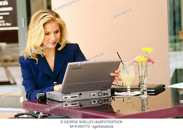 woman at a cafe with a computer