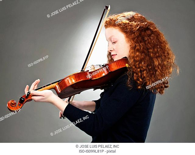 Portrait of mixed race teenage girl playing violin