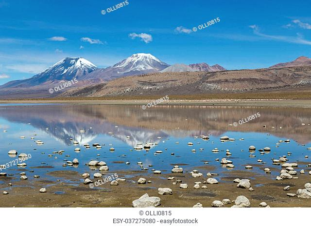 Photograph of a lake with reflection of Chilean volcanos in Sajama National Park, Bolivia