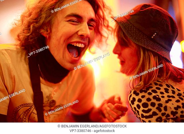 man screaming next to woman at night, nightlife