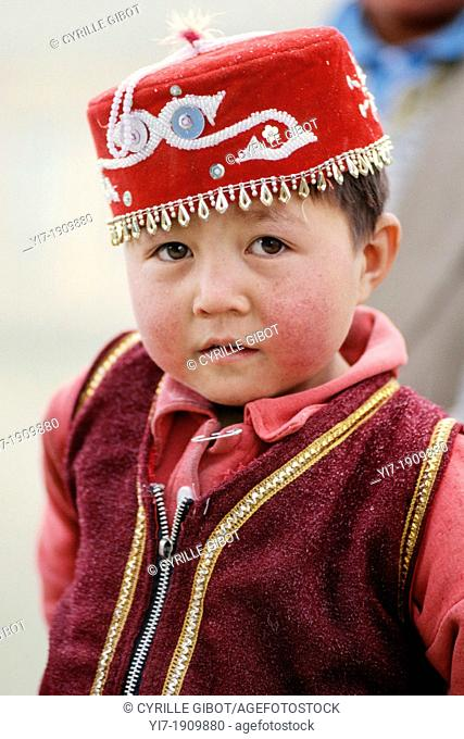 Little Kyrgyz boy in traditional clothing, Karakol Lake, Xinjiang province, China. The Kyrgyz form one of the 56 ethnic groups officially recognized by the...