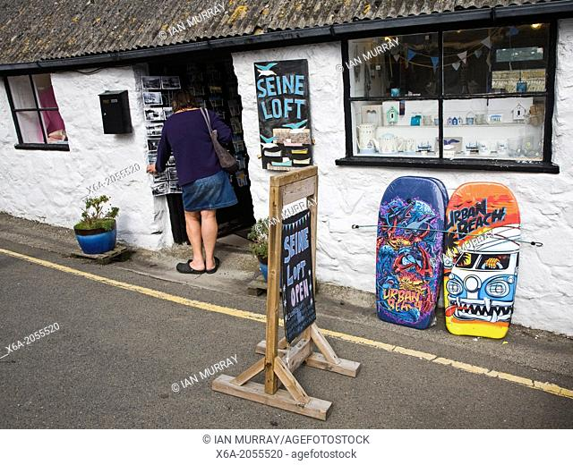 Woman browsing at a gift shop in village of Coverack, Cornwall, England
