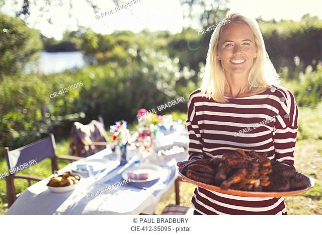 Portrait smiling woman serving platter of food at sunny garden party patio table