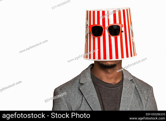 Anonymous African American man wearing striped popcorn bucket with sunglasses on head against gray background