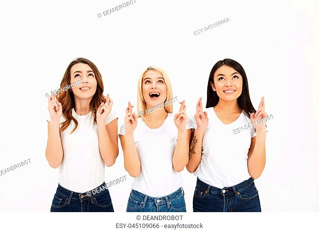 Portrait of three excited casual girls holding crossed fingers for good luck isolated over white background