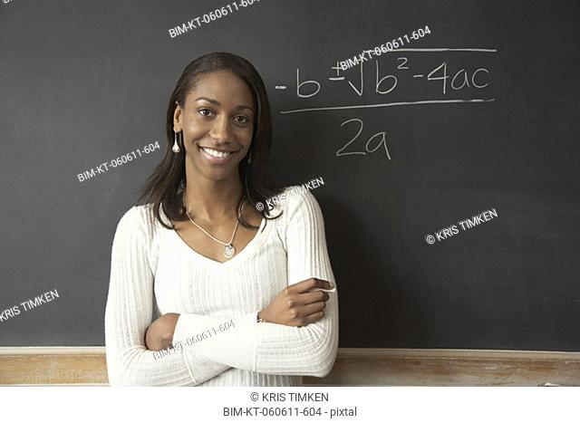 African female student next to math problem on blackboard