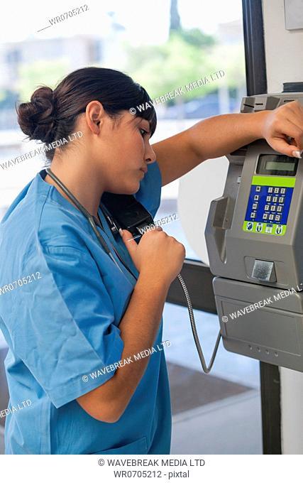Nurse using a hospital phone box