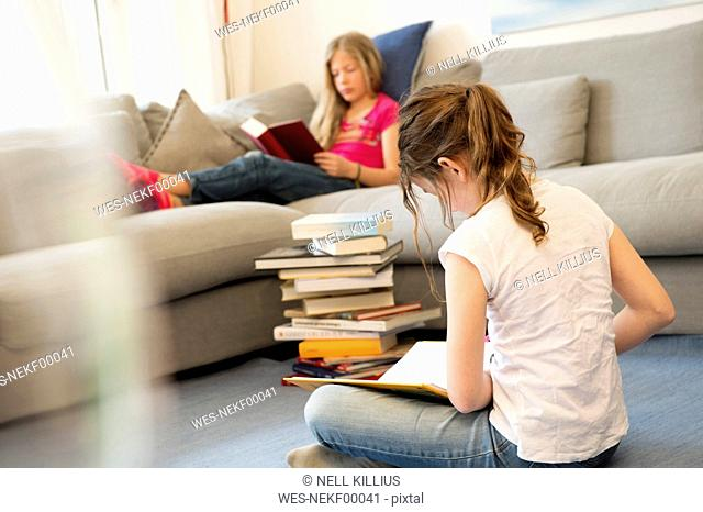 Two girls sitting in the living room reading books