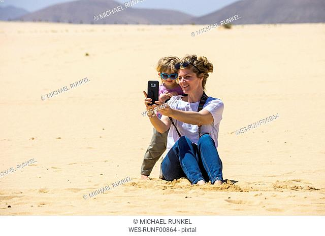 Spain, Canary Islands, Fuerteventura, Parque Natural de Corralejo, mother and daughter taking a selfie in sand dunes