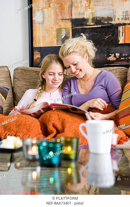 Mother and daughter in a couch reading, Sweden