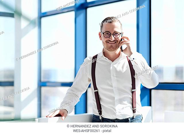 Smiling businessman talking on cell phone at the window in modern office