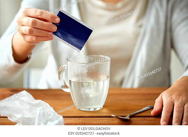 healthcare, medicine and people concept - close up of woman pouring medication into cup of water and paper tissue on wooden table