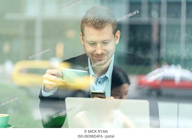 Businessman sitting in cafe, drinking coffee, using smartphone, viewed through window