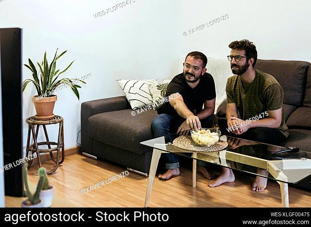 Male friends watching sports on TV while sitting over sofa in living room