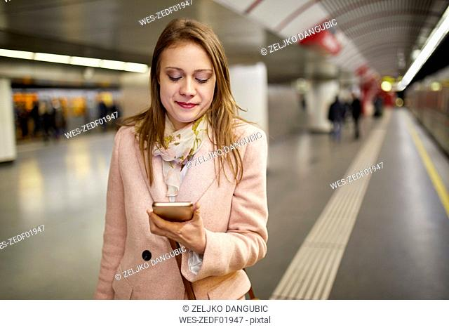 Austria, Vienna, portrait of smiling young woman looking at smartphone at underground station platform