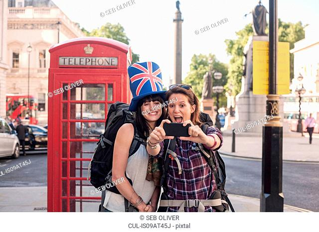 Two women backpackers taking smartphone selfie at red telephone box, London, UK