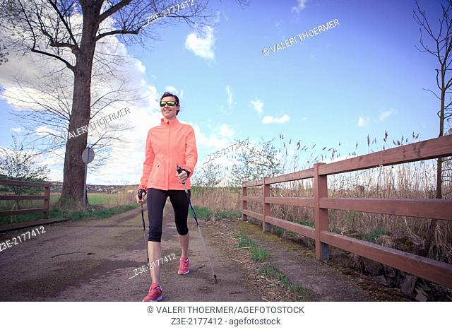 a woman nordic walking through the rural landscape near Coburg, Germany