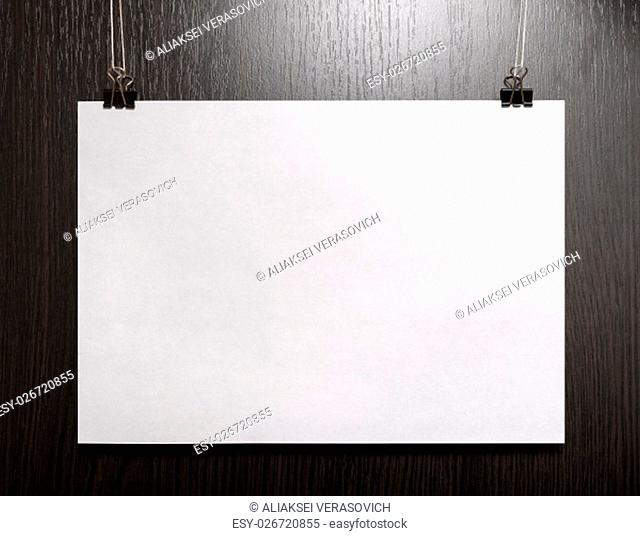 Blank horizontal paper poster hanging on dark wooden background. Front view