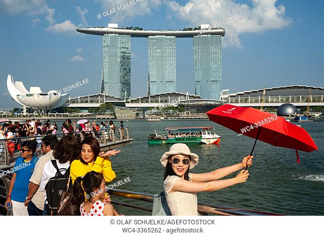 Singapore, Republic of Singapore, Asia - Tourists pose for photos at Merlion Park along the Singapore River with the Marina Bay Sands Hotel in the backdrop