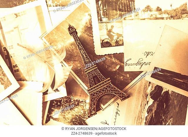 Old nostalgia in paris concept with a statue of the Eiffel Tower landmark placed against notes, letters photographs and feathers from past romances