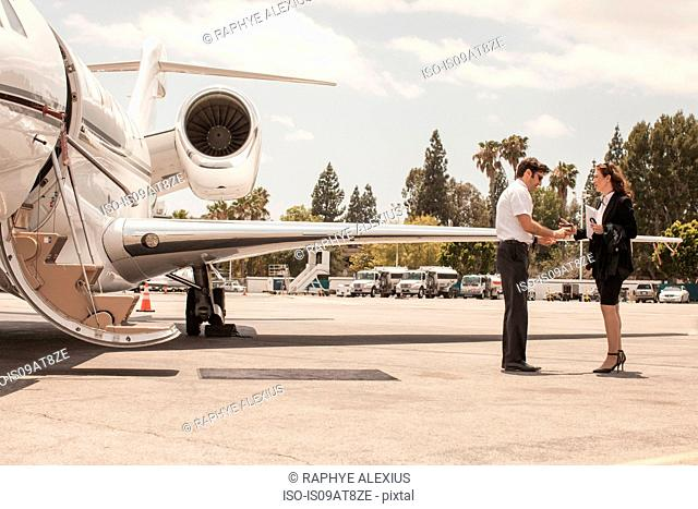 Female businesswoman shaking hands with private jet pilot at airport