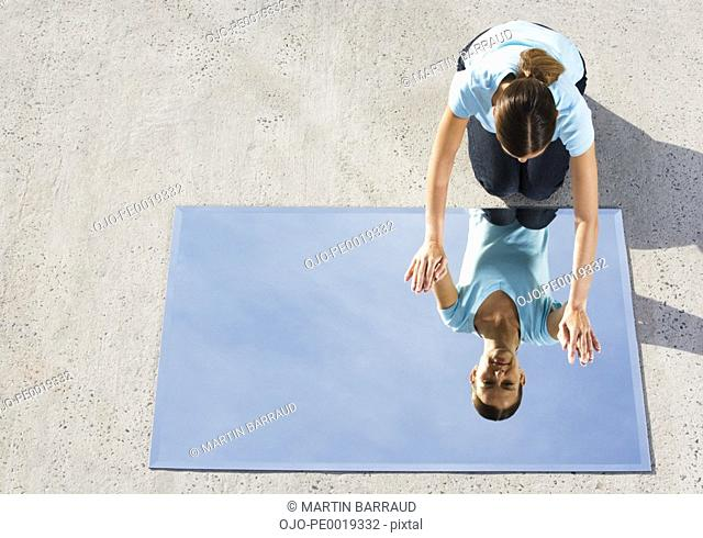 Woman kneeling on ground with mirror and reflection