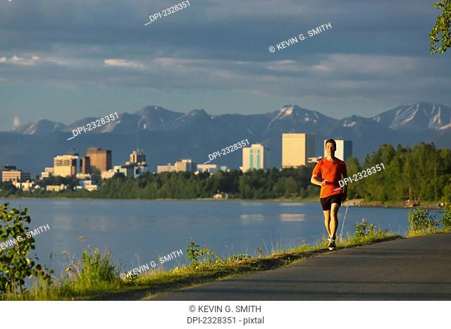 Man Jogging On The Tony Knowles Coastal Trail During High Tide With The Anchorage City Skyline, Knik Arm, And Chugach Mountains In The Background; Anchorage