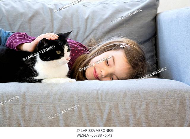 Little girl lying on couch stroking cat
