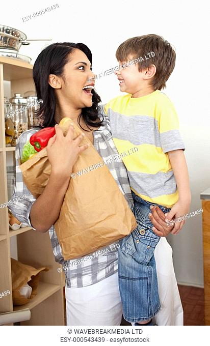 Cute Little boy unpacking grocery bag with his mother in the kitchen
