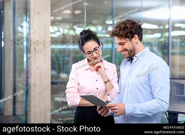 Young male entrepreneur with digital tablet discussing with female colleague against glass wall at office