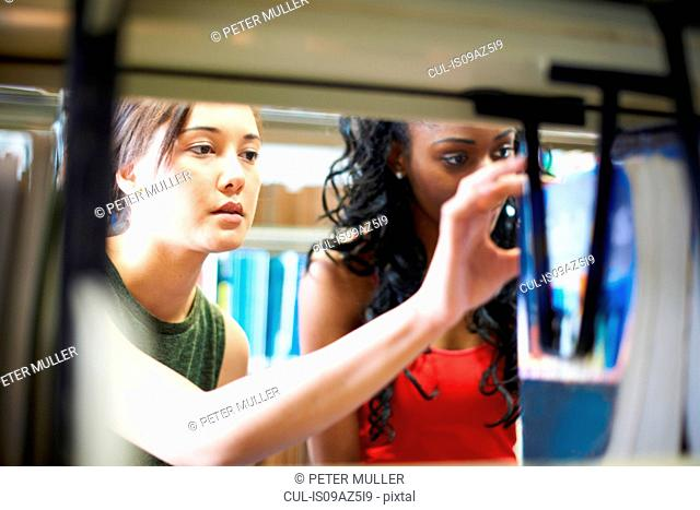Two young female college students searching library shelves