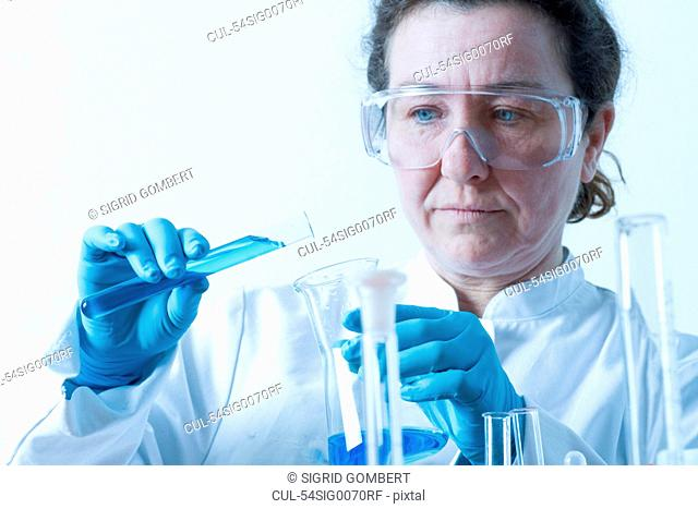 Scientist pouring liquid into beaker