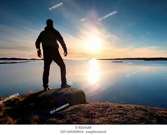 Young traveller standing on stone above sea and watching at sun. Rocky coast in silent bay