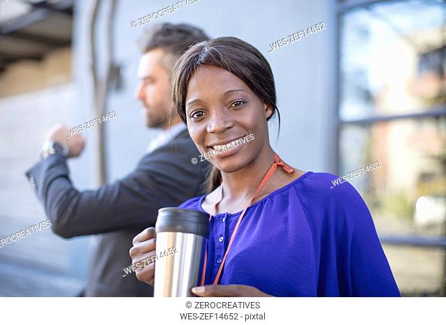 Portrait of smiling businesswoman with coffee mug and businessman in background
