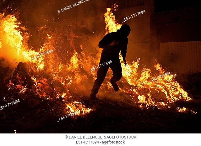 Young men jumping over a bonfire during San Antoni festival, Vilanova de L'Alcolea, Castellon, Spain
