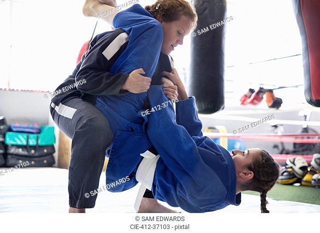 Determined women practicing judo in gym