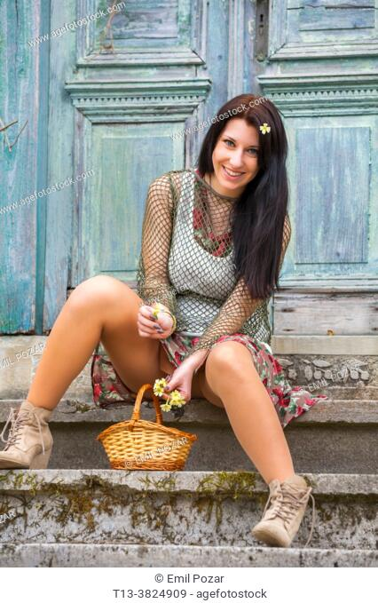 Countrygirl sitting on steps with flowers in basket
