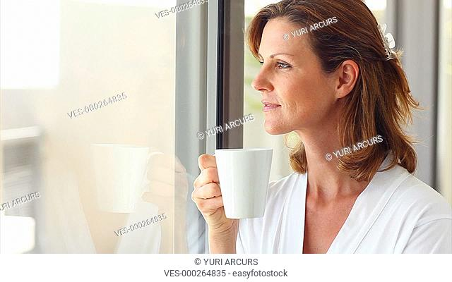 Pretty woman blows a hot cup of coffee while looking out her window in the morning