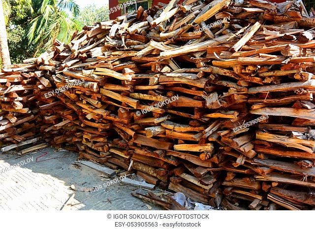 Woodpile of rare mahogany firewood in a Buddhist temple, Sihanoukville, Cambodia