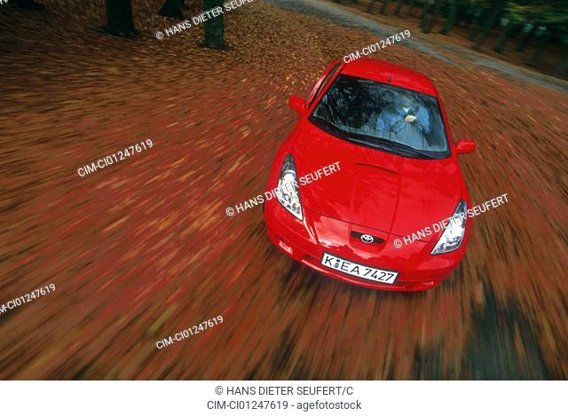 Car, Toyota Celiapprox.S 143 RS, roadster, coupe, model year 1999-, red, driving, diagonal from the front, frontal view, Foliage, Blätterwald