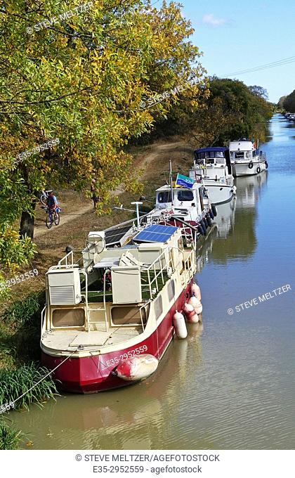 Houseboats, live-aboard boats anchored along the Canal du Midi at Capestang, France