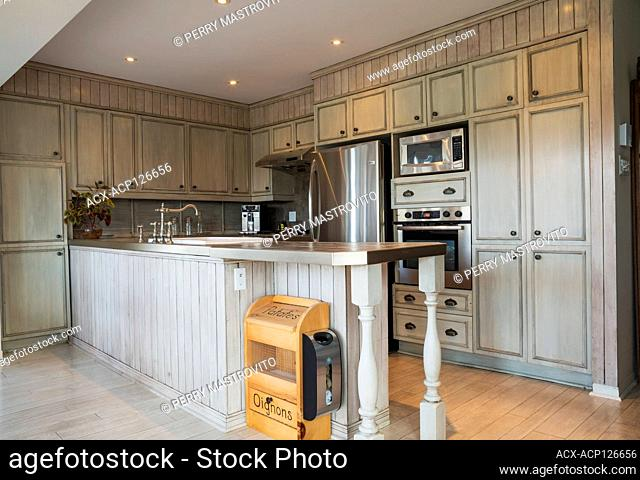 Country style kitchen with grey faux finish cabinets, ceramic countertop and plank wood imitation vinyl flooring inside an old 1820 cottage style fieldstone...
