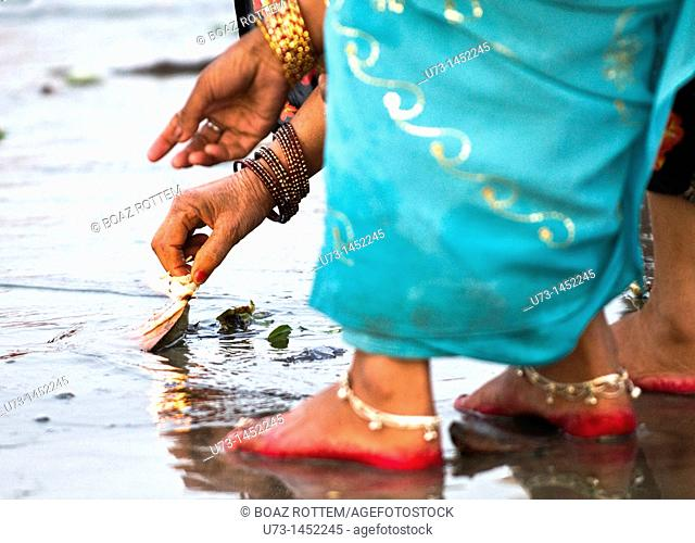 A woman lighting a candle during a puja ceremony in India