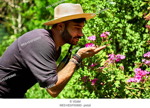 Man smelling flowers in garden
