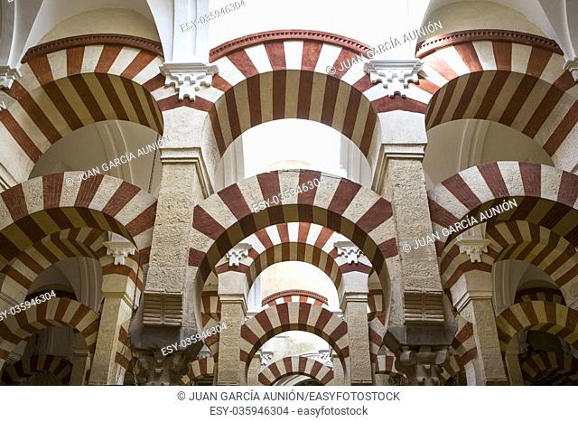Double red-and-white colored arches inside the Mezquita Mosque and Cathedral in Cordoba, Andalusia, Spain