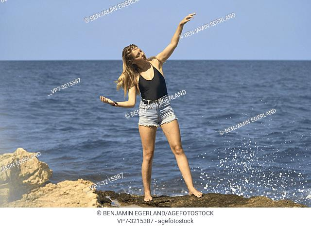 young woman stretching arms at seaside enjoying holiday and freedom, in Crete, Greece