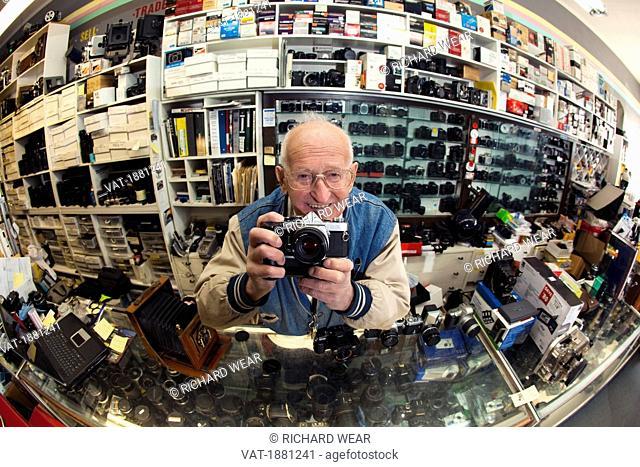 A Man Taking A Picture In A Camera Shop, Edmonton, Alberta, Canada