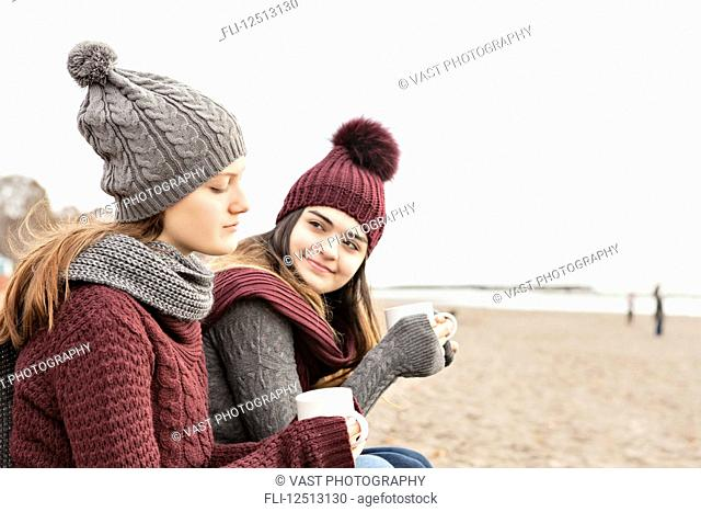 Two friends at the beach wearing knit hats and scarves, sitting and having coffee together, Woodbine Beach; Toronto, Ontario, Canada