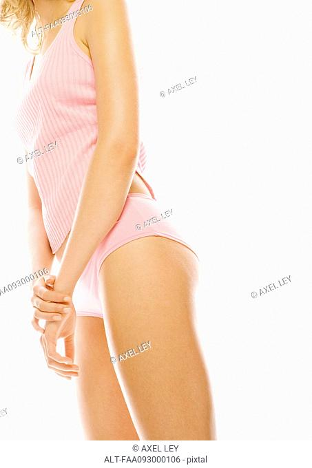 Young woman standing in tanktop and underpants, low angle, partial view